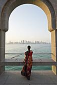Doha. Qatar. Vistitor looking across Bay of Doha from the Museum of Islamic Art.