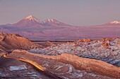 Valle de la Luna (Valley of the Moon ), in background at left volcanoes Licancabur and Juriques with snow on top, and salt deposited on the nearest mountains, Atacama desert. Region de Antofagasta. Chile.