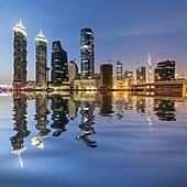 Futuristic skyline at night of new skyscrapers at Business Bay in Dubai United Arab Emirates.
