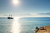 Antalya, Turkey. Looking west from entrance of Kaleici harbour. Fishermen and tourist sightseeing boat.