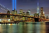 The Brooklyn bridge and Manhattan skyline at sunset, On September 11th, two blue beams (Tribute in Light) are the homage to the victims of 9-11-2011 attack to the World Trade Center, New York, USA