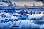 Midnight light at Jokulsarlon, a large glacial lake in southeast Iceland on the edge of Vatnajokull National Park. Situated at the head of the Breidamerkurjokull glacier, it developed into a lake after the glacier started receding from the edge of the Atl