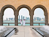 Two local men and skyline of Doha financial district at the Museum of Islamic Art in Doha Qatar.