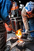 Takahiro Koizumi and his assistant Kohei ishimori are pouring molten iron into the mold, to make a iron teapot or tetsubin, nanbu tekki,Workshop of Koizumi family,craftsmen since 1659, Morioka, Iwate Prefecture, Japan.
