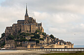 Abbey Mont-Saint-Michel, Unesco World Heritage, 2014 new bridge for pedestrians and shuttle buses, renaturation, mudflats, clouds, low tide, tourist attraction, Normandy, France