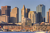 Early morning light reflects off the Custom House Tower, skyscrapers in the Financial District, and low rise wharves on the waterfront which make up part of the eclectic skyline of Boston, Massachusetts, USA.