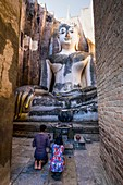 Asia. Thailand, old capital of Siam. Sukhothai archaeological Park, classified UNESCO World Heritage. Wat Si Chum. Couple kneeling praying in front of Buddha statue.