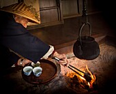 Tea shop owner adds charcoal to fire, ready to make tea for guests, Magome pilgrim trail, old post road between Kyoto and Tokyo, Japan.