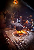 Chatting around fire in old mountain lodge, brazed trout on bamboos sticks in foreground, Kamikochi, Northern Japan Alps.