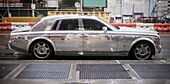 A silver, highly reflective Rolls-Royce automobile is parked in Lower Manhattan in New York