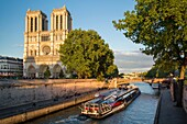 Dinner cruise barge sails up River Seine below Cathedral Notre Dame, Paris, France.
