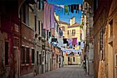 Laundry hanging across a narrow street in Venice, Italy.