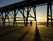 Jogger under Steetley pier at sunrise. The Headland, Hartlepool, north east England. UK.