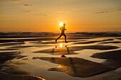 Jogger at sunrise on Seaton Carew beach, north east Enngland. United Kingdom.