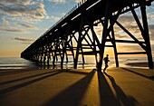 Jogger at sunrise under Steetley pier on The Headland, Hartlepool, north east England.