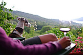 Young woman drinks a cup of wine at sunset in a terrace with views to the valley.