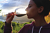 Young woman drinks wine at sunset in valley.