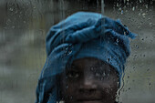 Little native girl standing behind a rain covered window, Sao Tome, Sao Tome and Principe, Africa