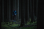 Young male runner standing in the forest and looking down, Allgaeu, Bavaria, Germany