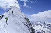Three persons back-country skiing ascending on steep slope to Care Alto, Care Alto, Adamello group, Lombardia, Italy
