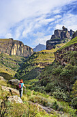 Woman hiking ascending through valley of Mashai River towards Sleeping Beauty Cave, Garden Castle, Mzimkhulu Wilderness Area, Drakensberg, uKhahlamba-Drakensberg Park, UNESCO World Heritage Site Maloti-Drakensberg-Park, KwaZulu-Natal, South Africa