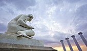 Sedent (seated), sculpture by Josep Llimona, and the Four Columns at Montjuïc. Barcelona. Catalonia. Spain.