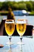 Enjoying a cold lager in beer garden. Riverside Pub. Norfolk Broads England UK.