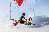 Puppet rowing in a boat under a balloon in the sky.
