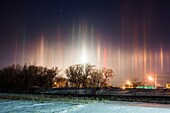 Arctic air combines with river steam and a corn milling plant´s steam to produce light pillars over Blair Nebraska, thanks to ice crystals floating in the air from the steam sources. A setting moon adds to the scene, creating a light pillar of its own.