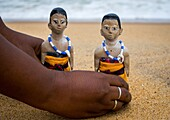 Benin, West Africa, Ouidah, mrs kpsouayo carrying the carved wooden figures made to house the soul of her dead twins on the beach.