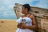 Benin, West Africa, Ouidah, mrs kpsouayo carrying the carved wooden figures made to house the soul of her dead twins.