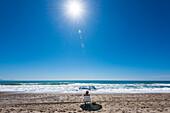 Ein Mann mit Stuhl und Sonnenschirm, bei strahlendem Sonnenschein und blauem Himmel, alleine am Strand, Torremolinos, Andalusien, Spanien