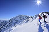 Two persons back-country skiing standing in notch in front of Breitenstein, Breitenstein, Chiemgau Alps, Chiemgau, Upper Bavaria, Bavaria, Germany