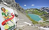 Sign with beer advertisement and lake Luenersee in background, lake Luenersee, Raetikon trail, Raetikon, Vorarlberg, Austria