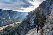 Group of hikers going down to Yosemite Point with the amazing view of the valley and the sunset, California, USA.