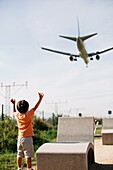 boy watching a plane landing at the Barcelona airport.