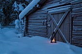 Old barn with lantern burning outside at the door, with snow on the ground and frost on the door, at time of dusk, Gällivare, Swedish Lapland, Sweden.