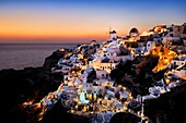 Windmills and village of Oia at sunset. Greece, Greek islands in the Aegean sea, the Cyclades, Santorini island (Thera, Thira).