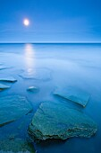 Algae covered rocks in Lake Ontario at dusk with a full moon. Oakville, Ontario, Canada.