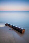 A long exposure creates a soft feel and mood to this image of a log washed ashore on a beach. Pinery Provincial Park, Ontario, Canada.