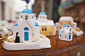 Souvenir blue domed church figurines on the bench for sell, Pyrgos, Santorini, Cyclades Islands, Greek Islands, Greece, Europe.
