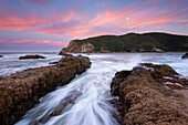Landscape photo of a colourful sunrise sky over the rocks at the Knysna Heads.Knysna, Western Cape, South Africa.
