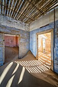 Photo of the interior of one of the old sand-filled buildings at the Kolmanskop mining Ghost Town. Kolmanskop, Luderitz, Namibia.