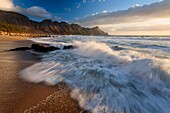 Landscape photo of a wave washing over a beach under dramatic sunset light. Kogelbay beach, Western Cape, South Africa.