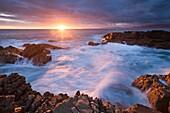 Landscape photo of a dramatic sunset on a rocky coastline. De Kelders, Western Cape, South Africa.