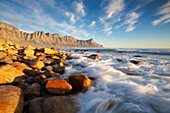 Landscape photo of a wave crashing against a rock. Kogelbay beach, Western Cape, South Africa.