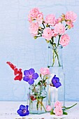 Glass containers filled with Geranium, Astilbi and miniture Rose flowers.