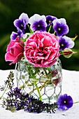 Roses and Viola flowers in glass vase.