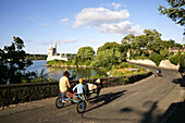 At the side of the River Lee, Two trotting carts pass down the small road to Blackrock Castle, Cork City, Ireland.