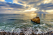 View of the ocean, sunbeams, and Bird Rock from Sunset Cliffs Natural Park. San Diego, California, United States.